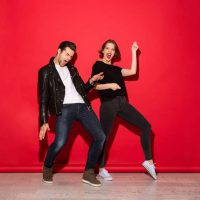 Full length image of playful punk couple dancing in studio over red background