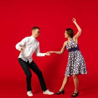 Rock n roll. Old-school fashioned young woman dancing isolated on red studio background. Artist fashion, motion and action concept, youth culture, fashion returning. Young stylish man and woman.